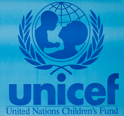 <p>Blue poster with light and dark blue lettering. Visual image is the logo for UNICEF, a silhouette of a woman holding up a baby against the background of a globe. 2 olive braches outline the globe. Title below image.</p>