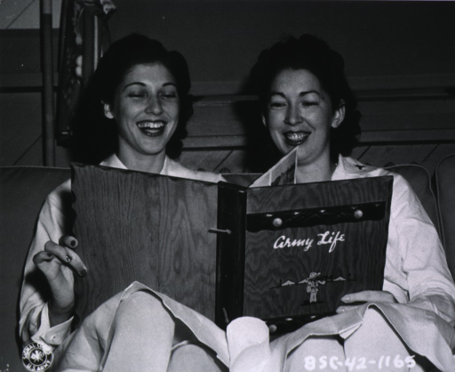 <p>Seated, full face; looking at album &quot;Army Life&quot;, with Sue Elliott.</p>
