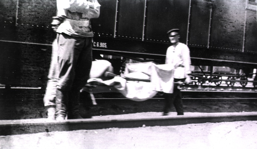 <p>A typhoid patient is carried on a litter to a hospital train.</p>