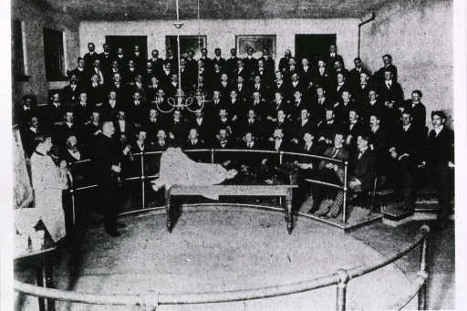 <p>Using a female mannequin situated in a delivery position, the instructor, holding forceps, is lecturing on delivery techniques. All of the medical students present are men.</p>