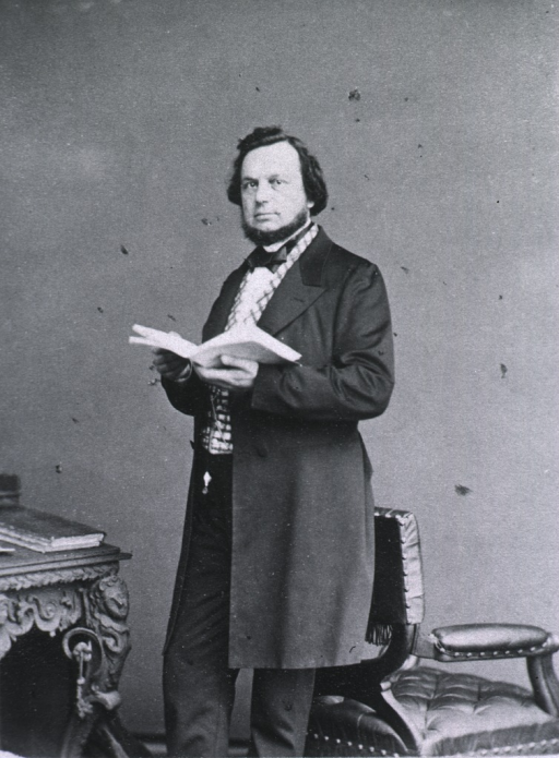 <p>Standing with back to a chair, holding an open book; left pose</p>