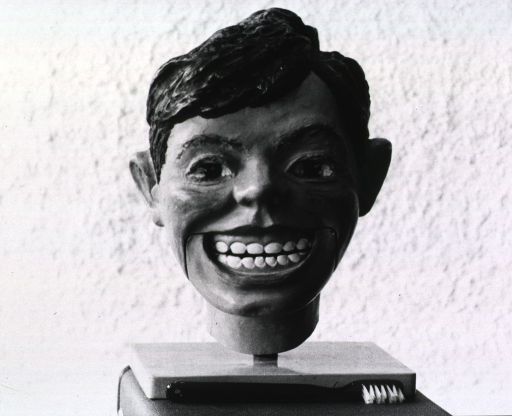 <p>Model of a human head with moveable jaw; the figure is smiling so that the teeth are exposed; a toothbrush, used in demonstrations, is in front of the model.</p>