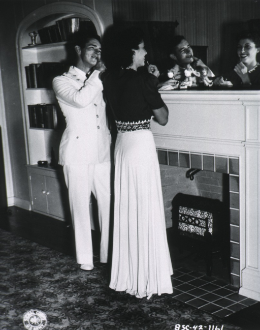 <p>Full length, right profile; wearing evening gown; looking into mirror; with escort 2nd Lieut. Charles W. Reese.</p>