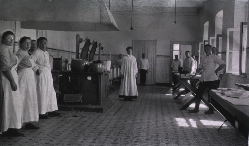 <p>Male and female staff stand in the kitchen of the Naval Hospital.</p>