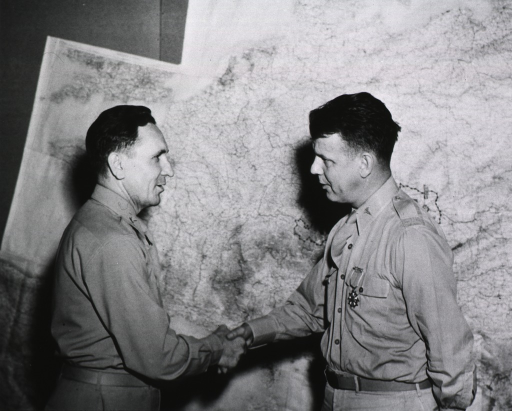 <p>The two servicemen stand in profile shaking hands in front of a large wall map of Europe.</p>