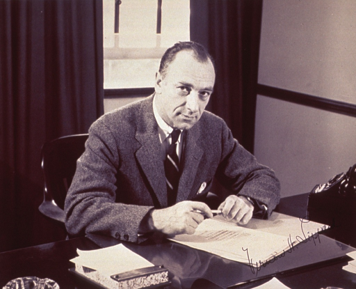 <p>Half-length, seated at desk, right pose, full face; arms resting on desk; holding a pencil.</p>