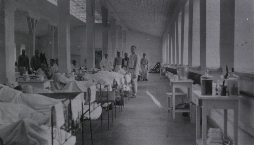 <p>Patients, medical personnel and a priest in a ward at Kaufman No. 2 Red Cross Hospital.</p>