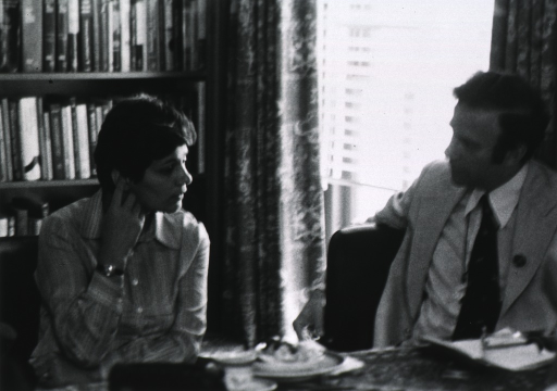 <p>Avital Scharansky, wife of Anatoly (Natan) Schanasky, is seated at a table speaking with a man.  There is a bookcase behind her.</p>