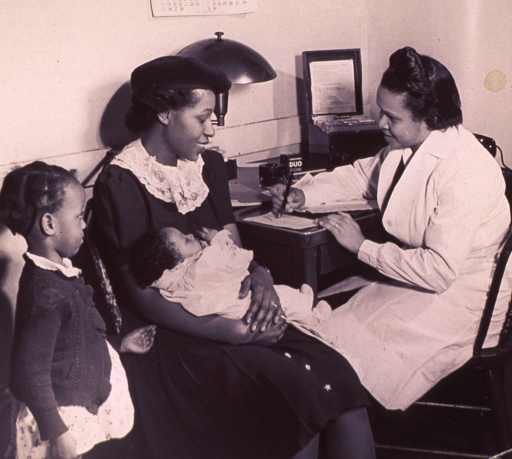 <p>An African American nurse is recording a medical history as it is reported by a woman holding an infant.</p>