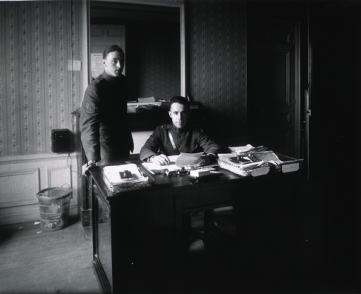 <p>Interior view of Medical Department showing Lt. Glover seated at desk, full face, and an unidentified sergeant standing next to the desk.</p>