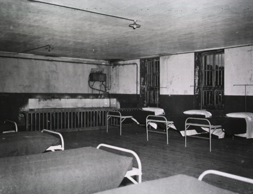 <p>Unoccupied single beds line the walls of a room.</p>