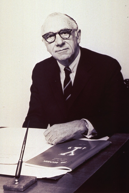 <p>Half-length, seated at desk, left pose, full face, wearing glasses; left arm resting on desk next to a reunion program for the &quot;20th Reunion Class of 1949 Yale University.&quot;</p>