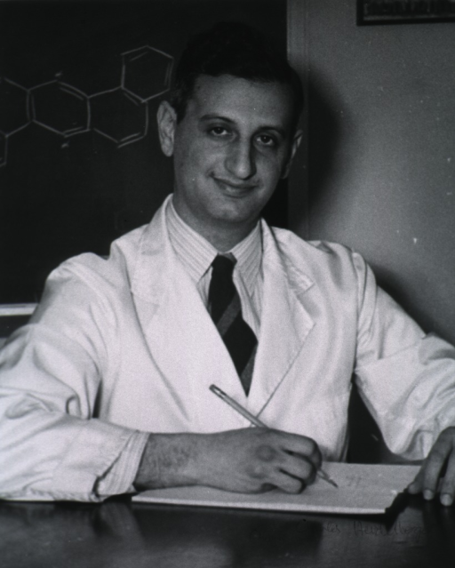 <p>Half-length, seated, right pose, full face; wearing white lab coat; holding pencil; blackboard in background.</p>