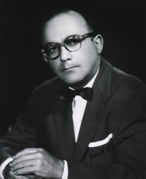 <p>Head and shoulders, half length, left pose, full face; wearing glasses, arms on table.</p>