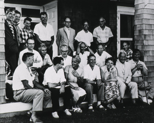 <p>Full length, full face; seated in front row (second from right) of group of 20 people - outside a house.  Possibly at Int. Congr. of Quantum Biology.</p>