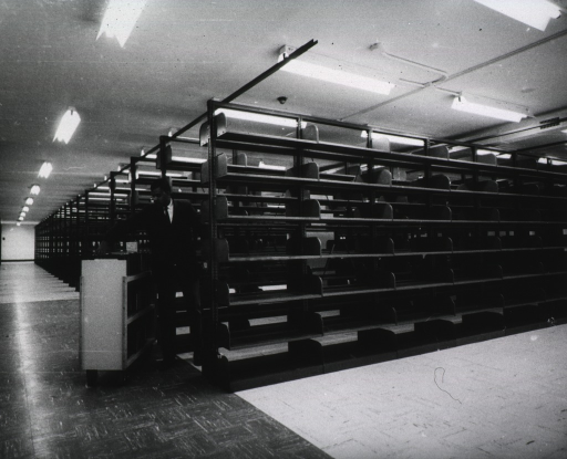 <p>Interior view: Mr. Weinstock and a book truck are at the beginning of the rows of empty shelves.</p>