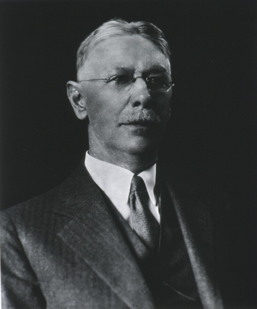 <p>Head and shoulders, full face, wearing suit, looking up snd to the right.</p>