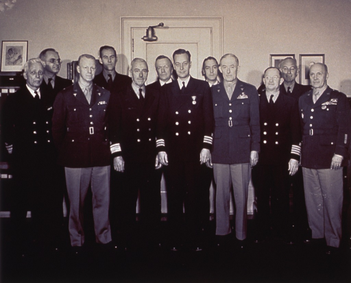 <p>A group of officers (some of which are unidentified) in uniform standing full length in an office; Topping is in the center of the group.</p>