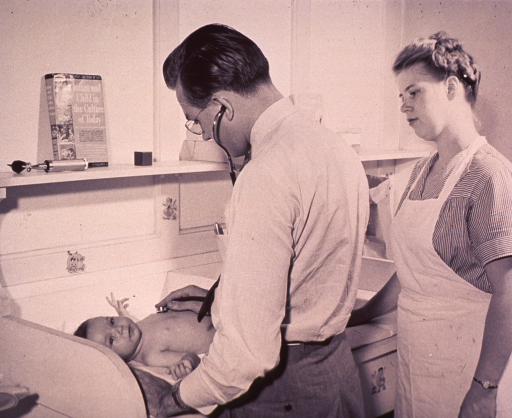 <p>A physician with a stethoscope is examining an infant; a nurse observes.</p>