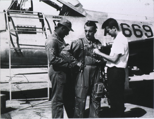 <p>With two other men, Dr. von Beckh in center, airplane in background.</p>