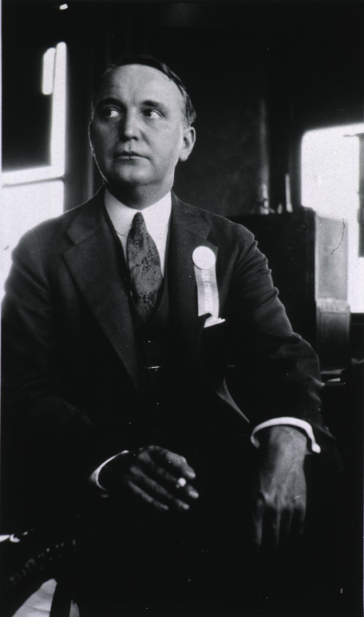 <p>Seated with hands resting on knees, holding cigar in right hand.</p>