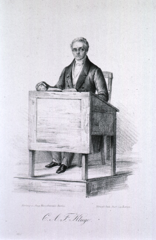 <p>Full length, seated behind desk, left pose, full face.</p>