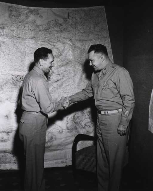 <p>Two servicemen stand in profile shaking hands in front of a large wall map of Europe.</p>