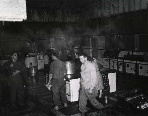 <p>Subect:  Servicemen and women at work in the high-ceilinged kitchen.</p>