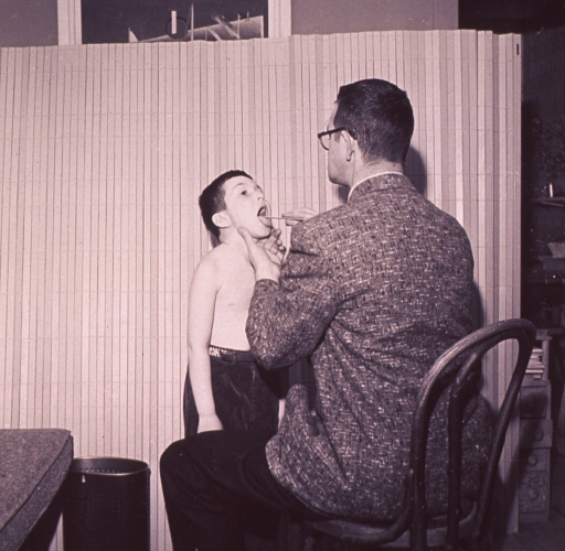 <p>A physician using a tongue depressor is examining a boy's throat.</p>