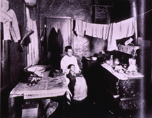 <p>A tenement mother and her child sit beside a table in their dark kitchen, wood burning stove to right and laundry on a line above.</p>