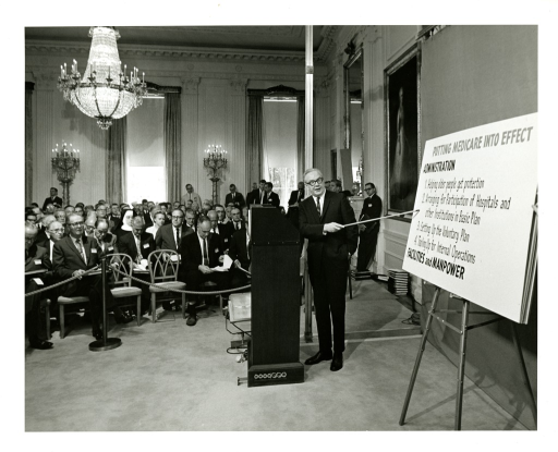<p>Robert M. Ball, Commissioner of the Social Security Administration, addresses a White House audience on the topic of Medicare in 1965.</p>