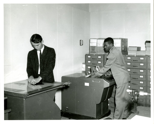 <p>Donald Dodson (left) operates a light table while Tyrone Ferguson (right) utilizes a Kodak Listomatic camera in the Bibliographic Services Division of the National Library of Medicine.</p>