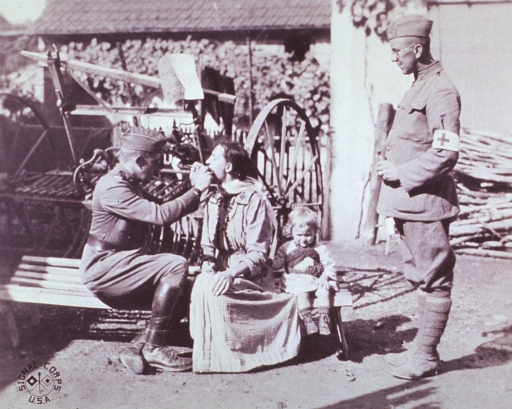<p>American medical officer examines the throat of a French woman that has lost her voice.</p>