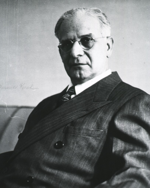 <p>Three quarter-length, seated, left pose, full face; wearing glasses.</p>