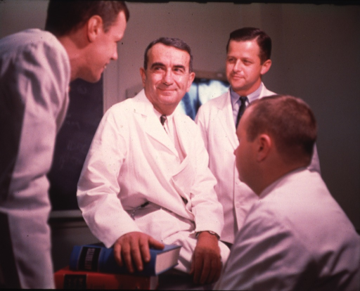 <p>Half-length, seated, right pose, full face; wearing white lab coat; with three colleagues.</p>