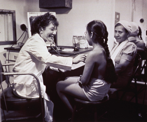 <p>A physician with a stethoscope is examining a young girl.</p>