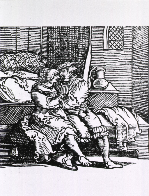 <p>Interior view: a man and a woman are sitting, in a romantic embrace, on a bench at the foot of a bed.</p>