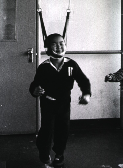 <p>A young boy is wearing a brace that is suspended from an overhead frame (not shown); the purpose of which may be to relieve pressure on the spine.</p>