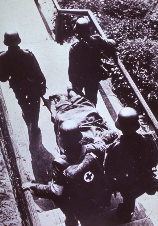 <p>Showing a wounded soldier being carried on stretcher to the rear of the German lines.</p>