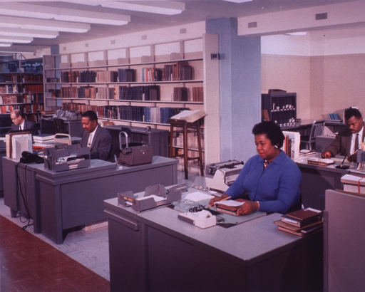 <p>Interior view: Mattie White, Mr. Richardson, and Mr. Green are sitting at their desks.  Phillip Coleman is sitting behind Mattie White.  Book shelves are behind Mr. Richardson and Mr. Green.  A dictionary on a stand is in front of the shelves.  There are typewriters by some of the desks, and an ashtray on Mattie White's desk.</p>