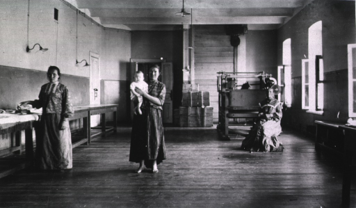 <p>Three women, one holding a child, in the laundry room at the Naval Hospital.</p>