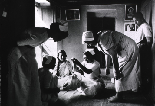 <p>Interior view of Southeast Asian nurse training center: nurse candidates are sitting on the floor, one of them is weighing a baby using a measuring device attached to a sling; an instructor is standing nearby.</p>