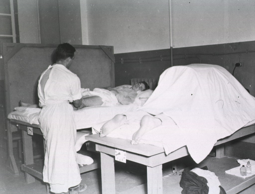 <p>A male therapist treats a serviceman who lies on a hospital bed.  Next to them is another hospital bed on which a patient lies obscured.</p>