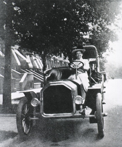 <p>In turn of the century dress, driving an automobile down a residential street.</p>
