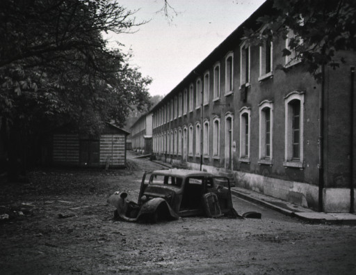 <p>A stripped car sits next to a long, two-storied building.</p>