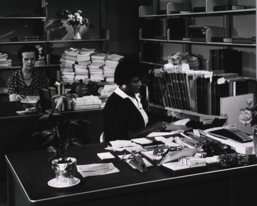<p>Interior view: Bound materials are on a book truck and on the shelves.  There is a plant and vases of flowers.  Unbound material is on a book truck behind the typewriter.</p>