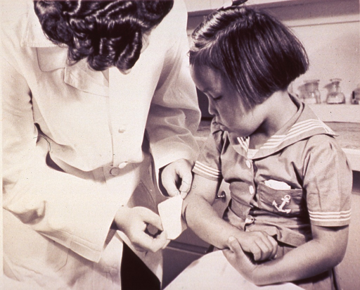 <p>A young girl receives a bandage for a bruise on her elbow.</p>