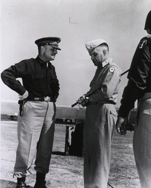 <p>The two servicemen stand outside in daylight and chat.  Oxx holds a crop under his left arm.  A third serviceman stands with his back to the camera and watches.</p>