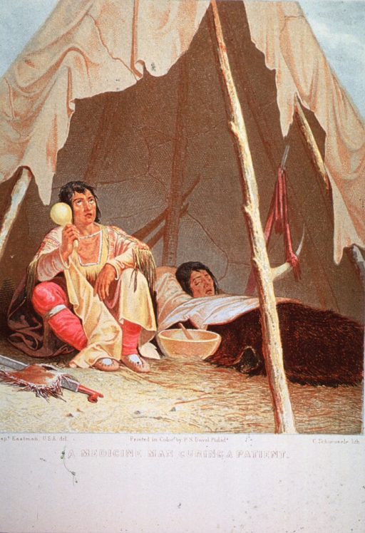 <p>A medicine-man, holding a gourd rattle, is sitting in a tepee with a patient; there is a large bowl on the ground between them.</p>