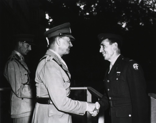 <p>The two servicemen shake hands on an outdoor dais at dusk.  Another serviceman stands behind them and looks down.</p>